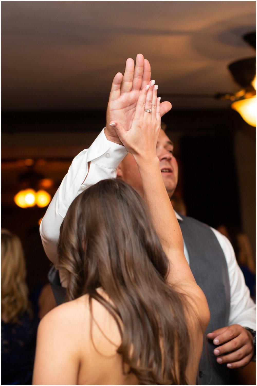 Katie high-fives one of the groomsmen on the dance floor.