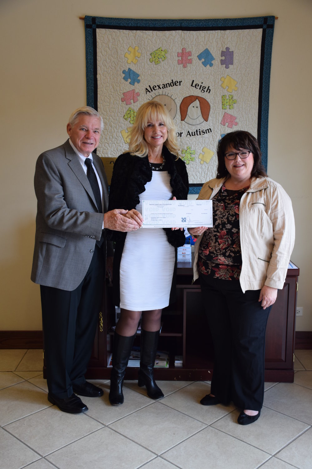 Kelly Weaver (right) with Bill and Susan Bovinette of Life Guys Inc., presenting the NAILBA foundation check for $25,000.