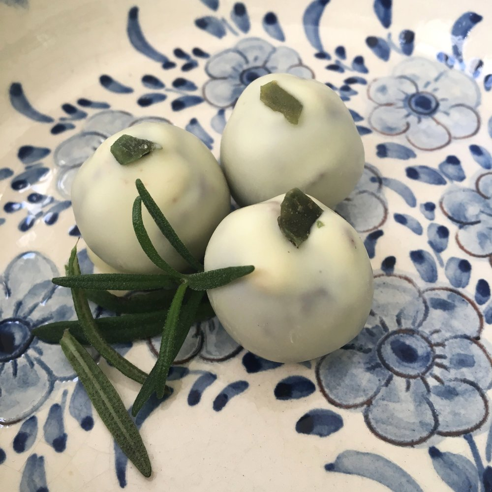 Rosy Goat - A delicious tangy twist - organic homegrown rosemary infused mild goat cheese blended into milk chocolate ganache and dipped in white chocolate. Finished with a sweet crystallized piece of mint leaf.