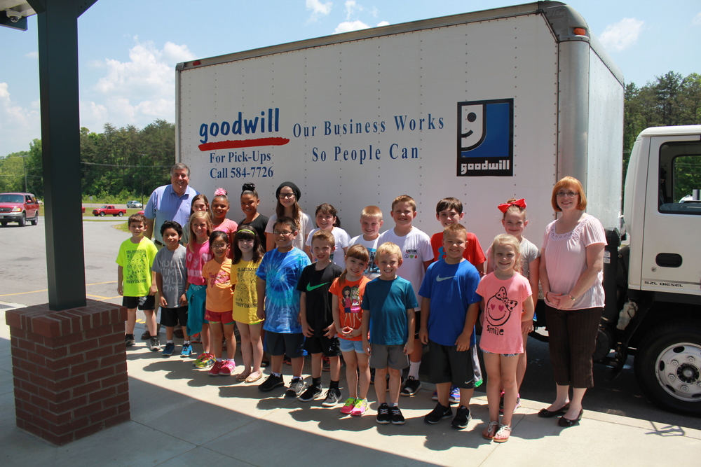 Knox County's Carter Elementary School Safety Patrol students volunteer to load collected donations into the Goodwill truck at the Straight from the Heart Sack Pack Kickoff. Above, they pose with Bob Kesling and Goodwill's Michelle Bush.
