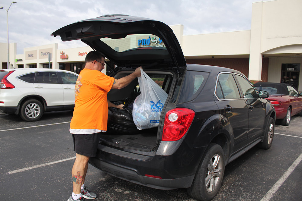 Marty helps load donations that he has collected at J&L Cleaners for Project Wear and Share.