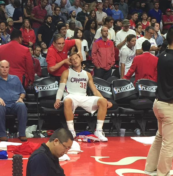 Clipper's chiropractor adjusting Blake Griffin's neck at the end of the third quarter during a NBA match.