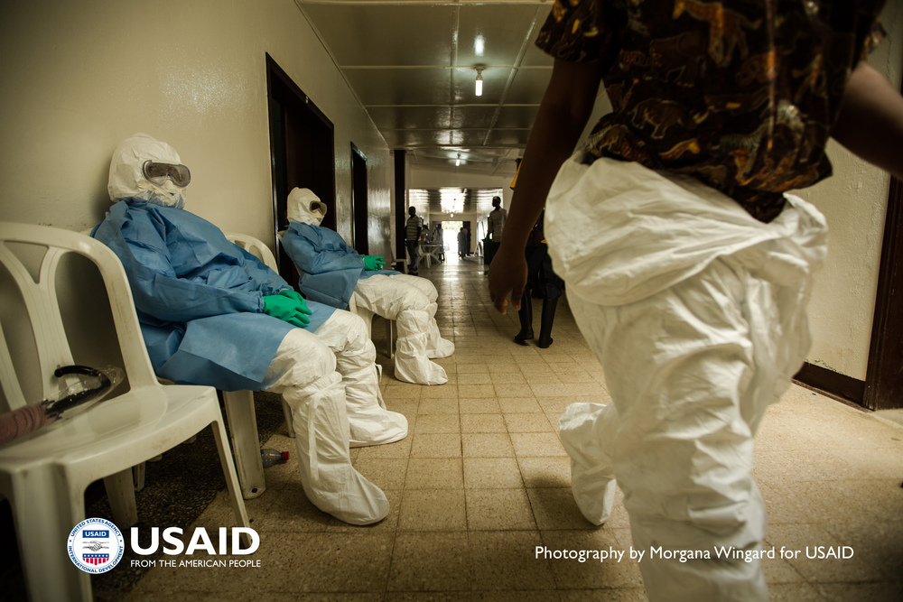 Health workers in personal protective equipment (PPE) wait to enter the hot zone at Island Clinic in Monrovia, Liberia on Sept 22. 2014. PPE is their primary protection, but it is also the greatest source of stress. / Morgana Wingard, USAID