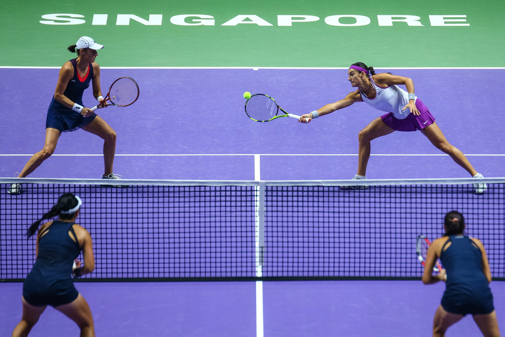 Caroline Garcia of France and Katarina Srebotnik of Slovenia in action against Chan Hao-Ching and Chan Yung-Jan of Chinese Taipei during their doubles match during the BNP Paribas WTA Finals at the OCBC Arena on October 26, 2015 in Singapore.
