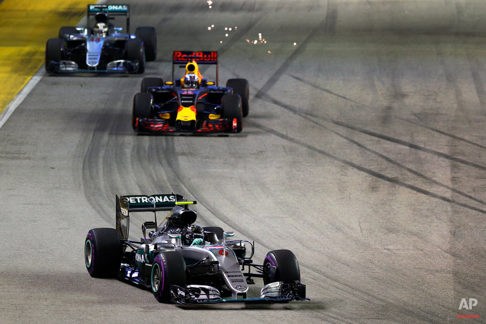 Mercedes driver Nico Rosberg of Germany, followed by Red Bull driver Daniel Ricciardo of Australia and Mercedes driver Lewis Hamilton of Britain, steer their cars during the Singapore Formula One Grand Prix on the Marina Bay City Circuit in Singapore, Sunday, Sept. 18, 2016. (AP Photo/Yong Teck Lim)