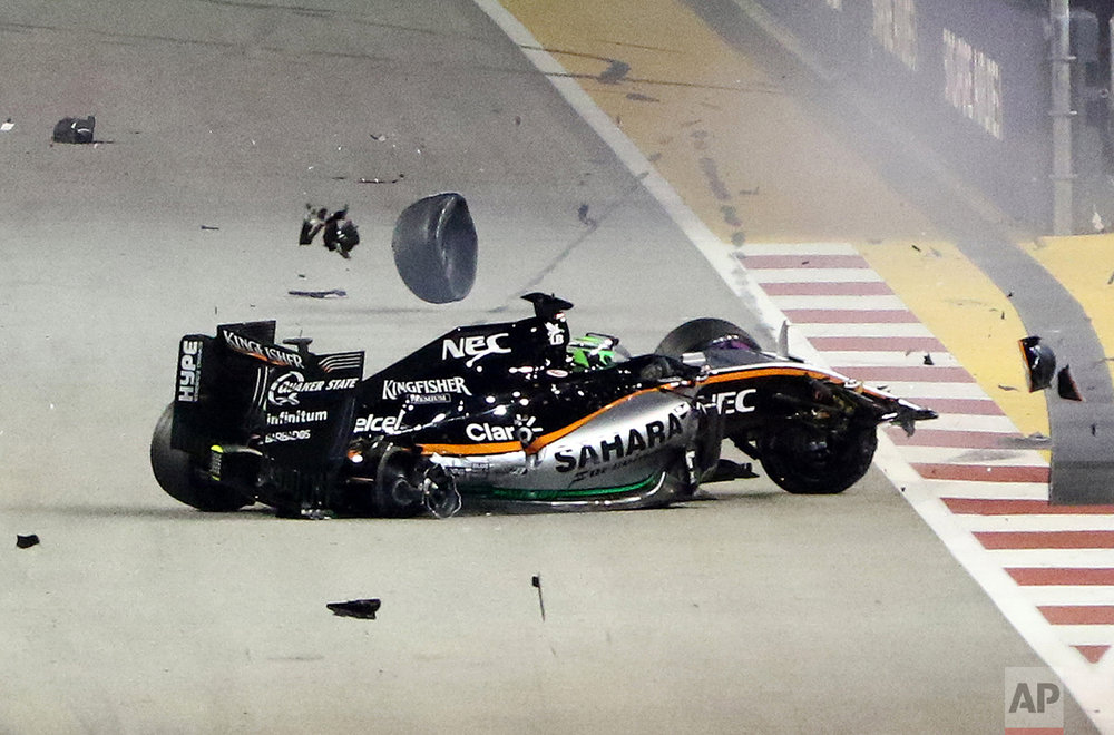 Debris flies off Force India driver Nico Hulkenberg of Germany's car after he crashed into the track wall at the start of the Singapore Formula One Grand Prix on the Marina Bay City Circuit Singapore, Sunday, Sept. 18, 2016. (AP Photo/Yong Teck Lim)