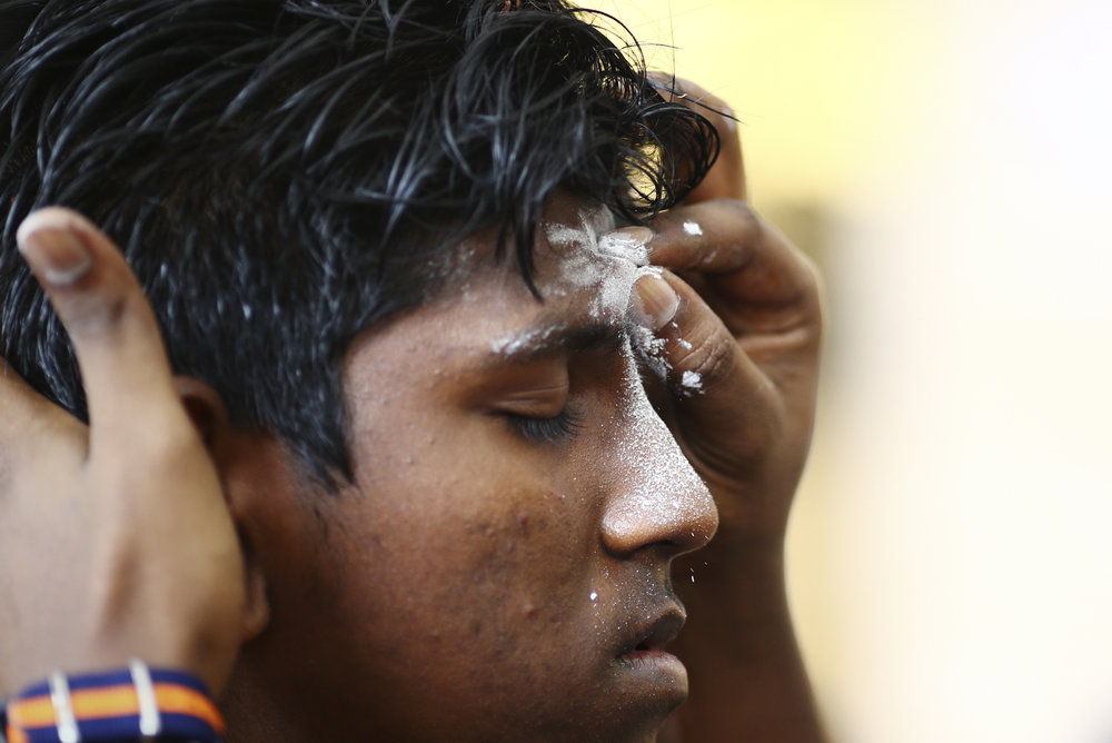 A devotee receives blessings from his family members during the Thaipusam festival at the Sri Srinivasa Perumal Temple on February 9, 2017 in Singapore.