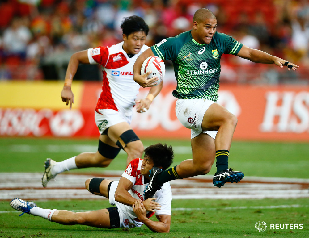 Rugby Union - Singapore Sevens - National Stadium, Singapore, 15/04/17 - South Africa's Zain Davids (R) tries to evade a tackle by Japan's Kosuke Hashino. REUTERS/Yong Teck Lim