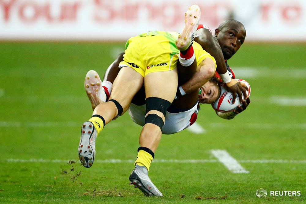 Rugby Union - Singapore Sevens - National Stadium, Singapore, 15/04/17 - Kenya's Frank Wanyama is tackled by Australia's Tom Lucas. REUTERS/Yong Teck Lim