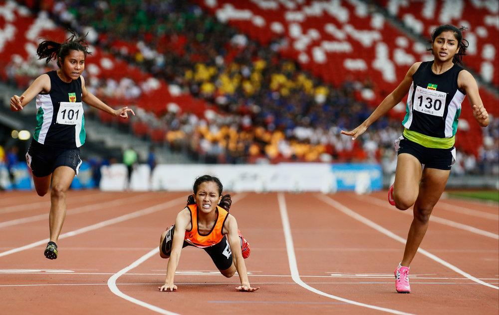 Tanisha Moghe (R) of Raffles Institution finishes in first place, while Ismi Zakiah (C) of Singapore Sports School stumbles at the finish line to finish second during the girls' 'A' Division 100m final of the 79th Singapore Open Track and Field Championships at the National Stadium on April 28, 2017 in Singapore.