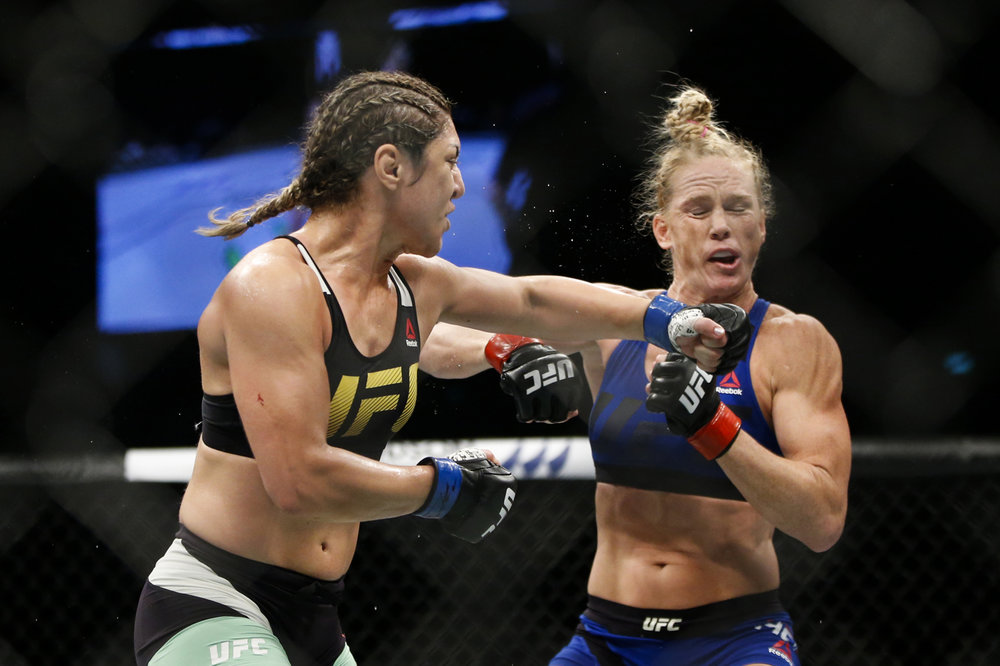 Bethe Correia (L) of Brazil punches Holly Holm of the United States during their bantamweight bout at the UFC Fight Night at the Singapore Indoor Stadium on June 17, 2017.