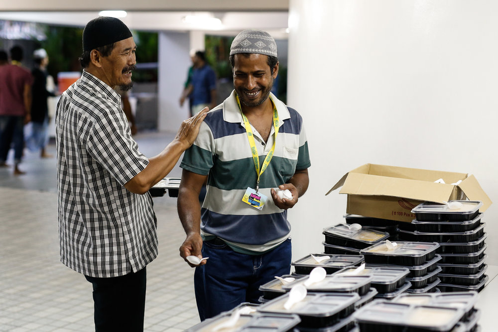 A volunteer (R) interacts with a member of the public at Masjid Al-Mukminin.