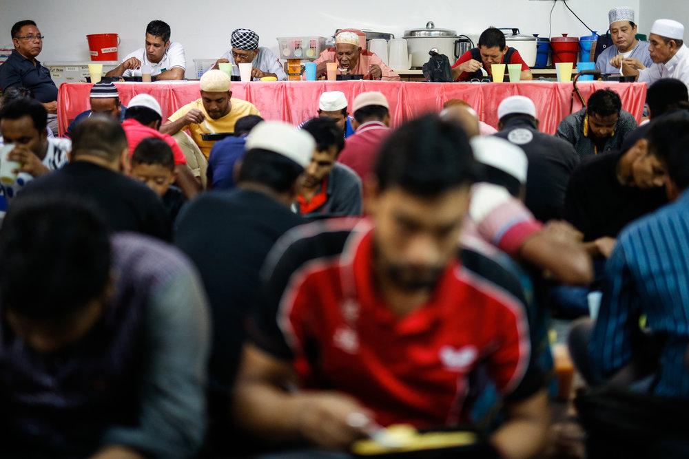Muslims eat their iftar meals at Masjid Al-Mukminin.