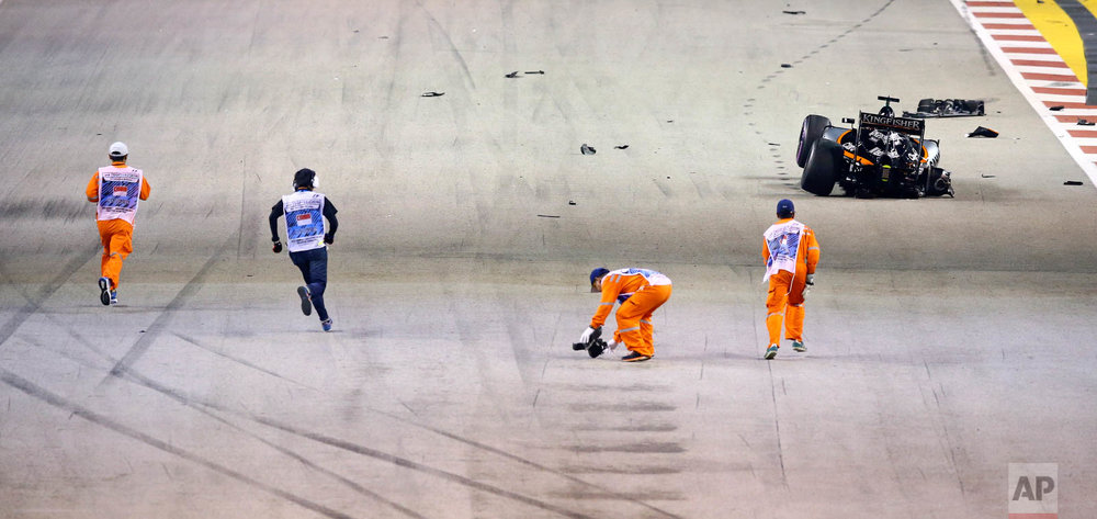 Track marshals clear debris from the track after Force India driver Nico Hulkenberg of Germany crashed at the start of the Singapore Formula One Grand Prix on the Marina Bay City Circuit in Singapore, Sunday, Sept. 18, 2016. (AP Photo/Yong Teck Lim)