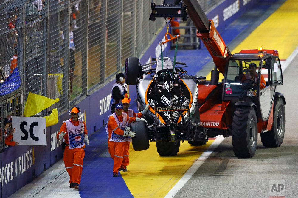 The car of Force India driver Nico Hulkenberg of Germany is taken from the track after he crashed at the start of the Singapore Formula One Grand Prix on the Marina Bay City Circuit in Singapore, Sunday, Sept. 18, 2016. (AP Photo/Yong Teck Lim)
