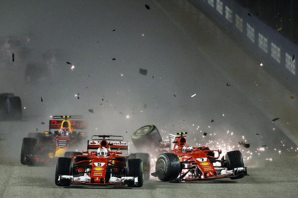 Ferrari driver Kimi Raikkonen, right, of Finland collides with teammate Sebastian Vettel of Germany at the start of the Singapore Formula One Grand Prix on the Marina Bay City Circuit Singapore, Sunday, Sept. 17, 2017. (AP Photo/Yong Teck Lim)