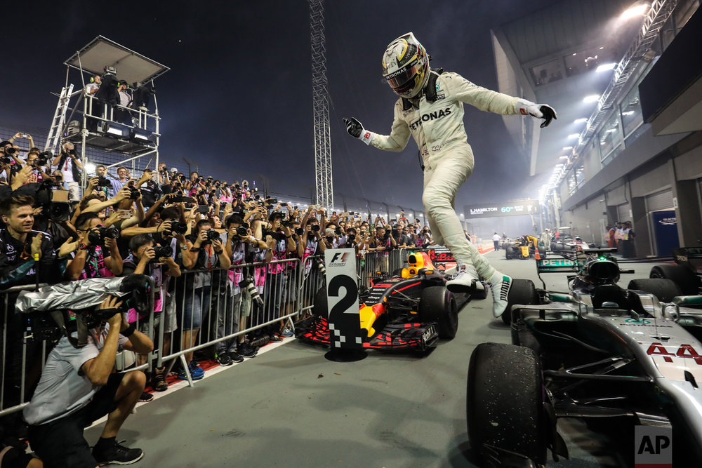 Mercedes driver Lewis Hamilton of Britain leaps off his car as he celebrates after winning the Singapore Formula One Grand Prix on the Marina Bay City Circuit Singapore, Sunday, Sept. 17, 2017. (AP Photo/Yong Teck Lim)