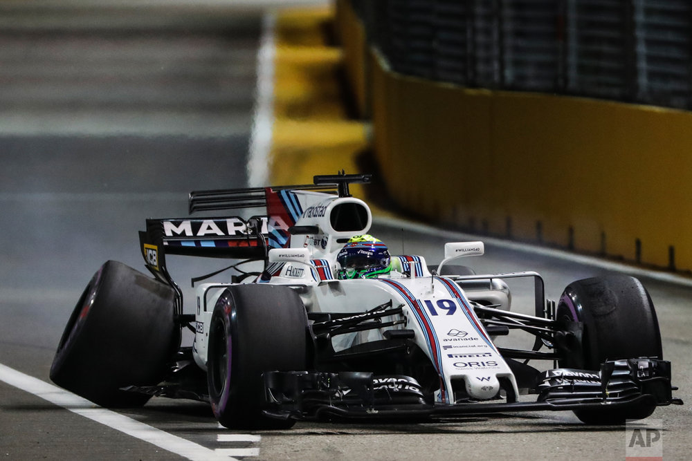 Williams driver Felipe Massa of Brazil steers his car with the rear wheel damaged after hitting the wall during the qualifying session for the Singapore Formula One Grand Prix on the Marina Bay City Circuit Singapore, Saturday, Sept. 16, 2017. (AP Photo/Yong Teck Lim)