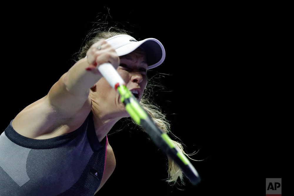 Caroline Wozniacki of Denmark serves the ball to Karolina Pliskova of the Czech Republic during her singles semifinal match at the WTA tennis tournament in Singapore, on Saturday, Oct. 28, 2017. (AP Photo/Yong Teck Lim)