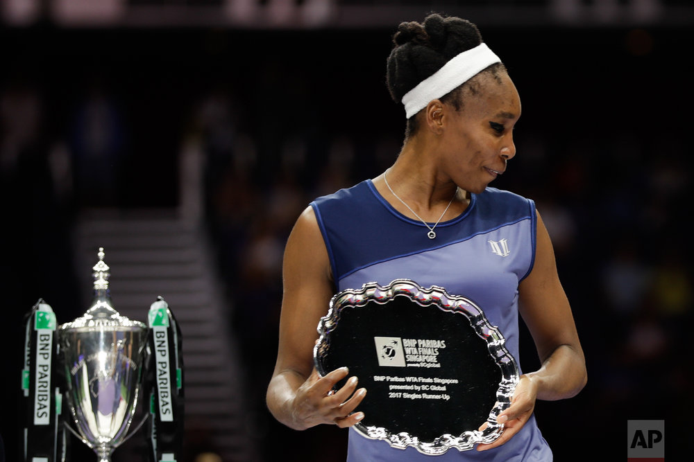 Venus Williams of the United States reacts with her runner-up trophy after conceding her singles final match to Caroline Wozniacki of Denmark at the WTA tennis tournament in Singapore, on Sunday, Oct. 29, 2017. (AP Photo/Yong Teck Lim)