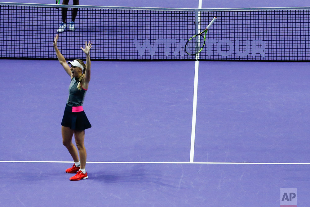 Caroline Wozniacki of Denmark celebrates after beating Venus Williams of the United States during their singles final match at the WTA tennis tournament in Singapore, on Sunday, Oct. 29, 2017. (AP Photo/Yong Teck Lim)