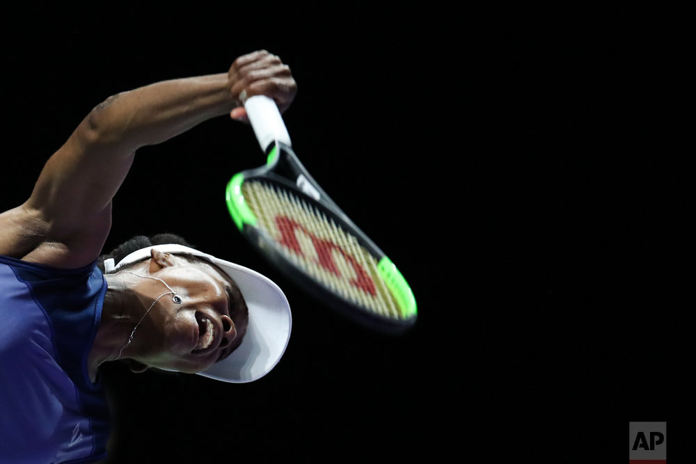 Venus Williams of the United States serves the ball to Caroline Garcia of France during their semifinal match at the WTA tennis tournament in Singapore, on Saturday, Oct. 28, 2017. (AP Photo/Yong Teck Lim)