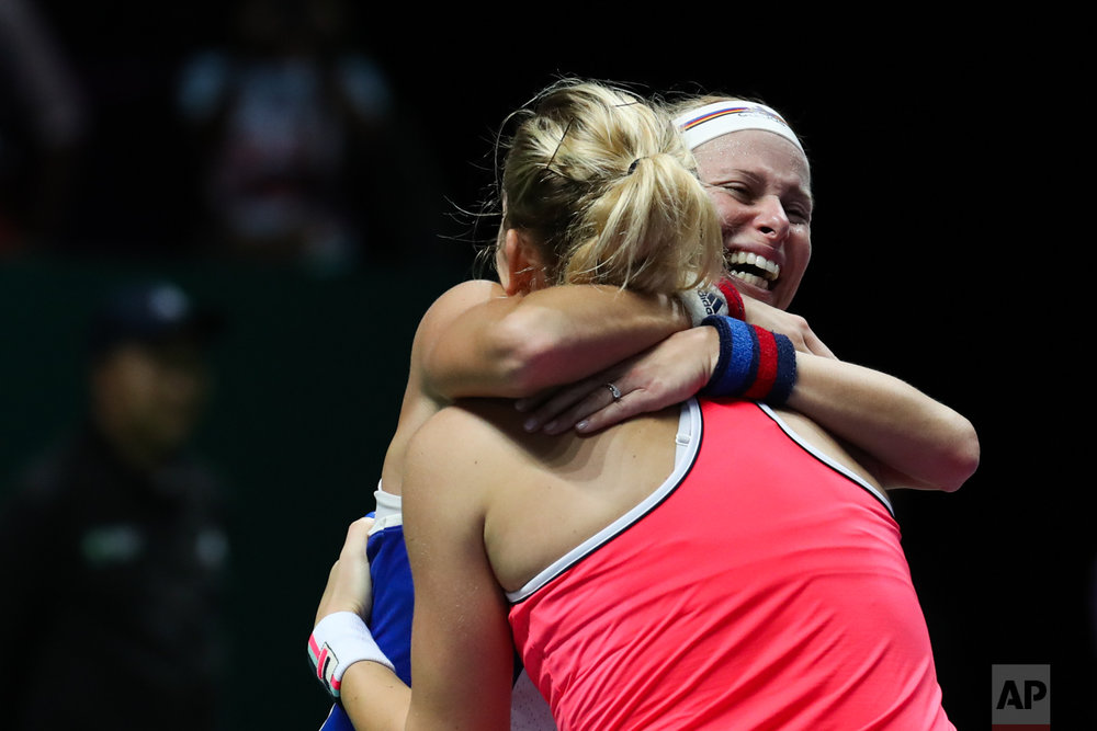 Andrea Hlavackova of the Czech Republic, right, and Timea Babos of Hungary celebrate after beating Kiki Bertens of the Netherlands and Johanna Larsson of Sweden during their doubles final match at the WTA tennis tournament in Singapore, on Sunday, Oct. 29, 2017. (AP Photo/Yong Teck Lim)