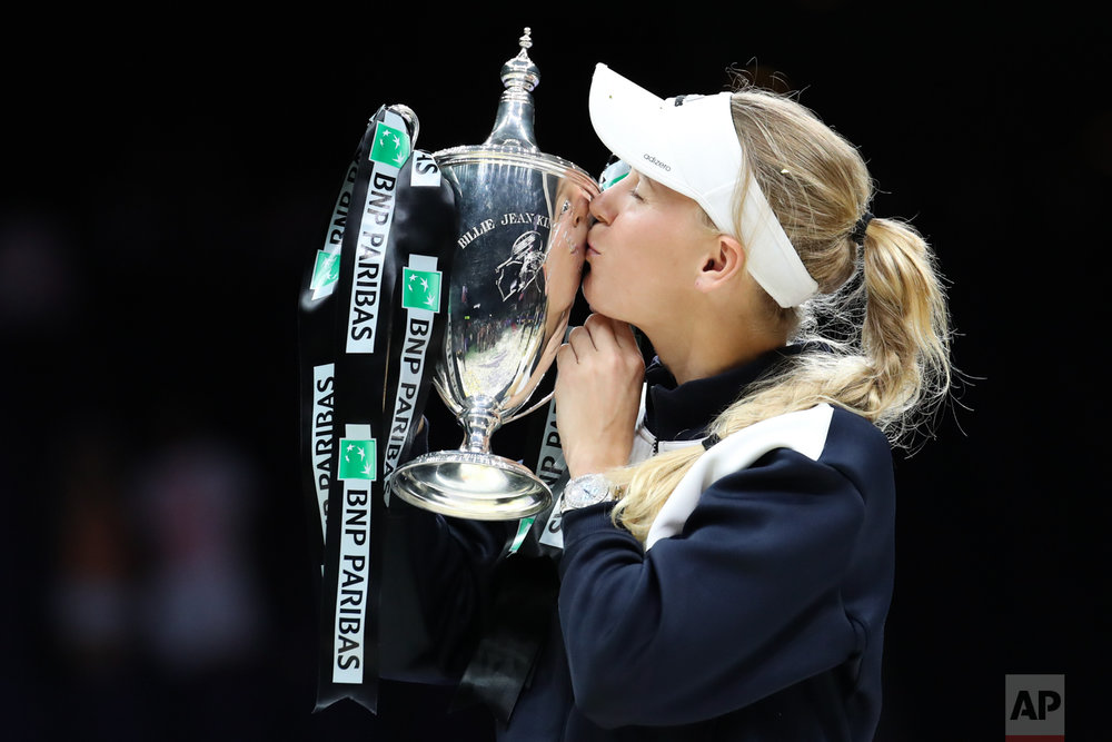 Caroline Wozniacki of Denmark kisses the winner's trophy after beating Venus Williams of the United States during their singles final match at the WTA tennis tournament in Singapore, on Sunday, Oct. 29, 2017. (AP Photo/Yong Teck Lim)