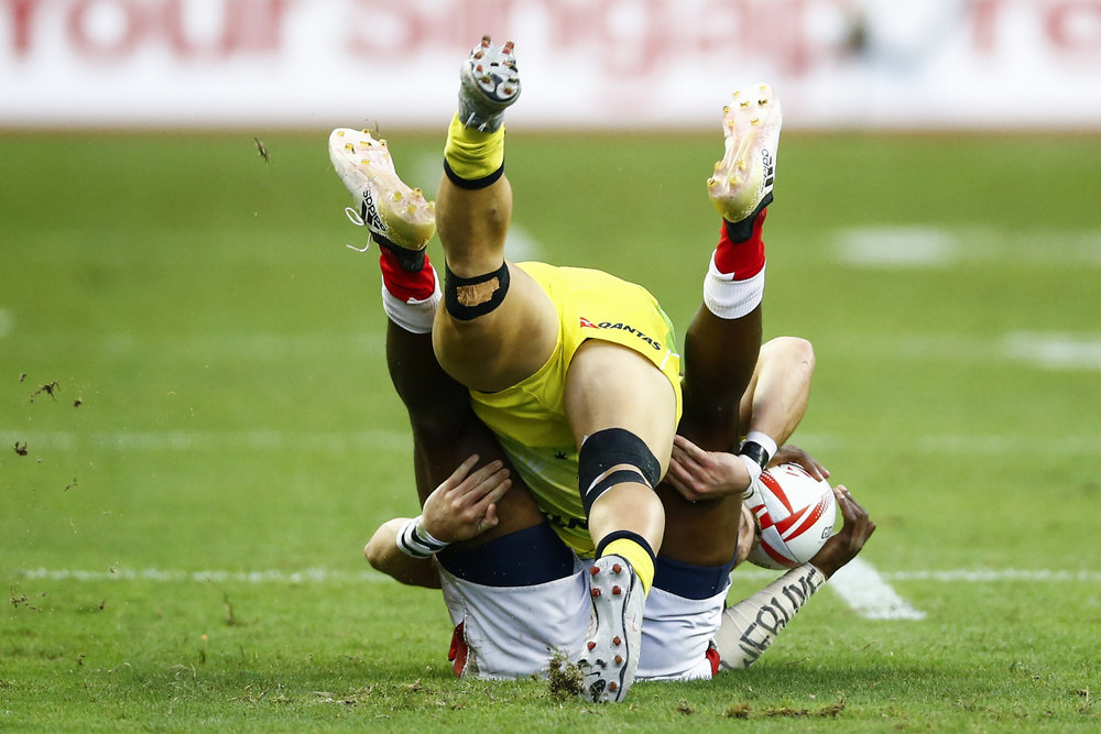 Rugby Union - Singapore Sevens - National Stadium, Singapore, 15/04/17 - Kenya's Frank Wanyama (bottom) is tackled by Australia's Tom Lucas.