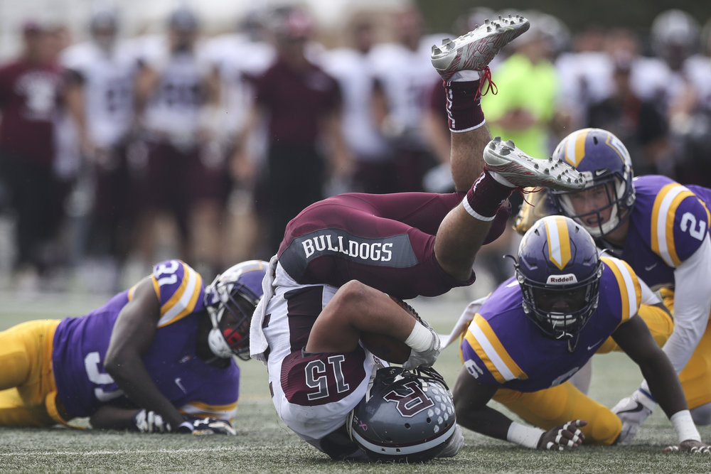 Josiah Alvira #15 of the Redlands Bulldogs falls after a tackle by the Cal Lutheran Kingsmen at the William Rolland Stadium on November 11, 2017 in Thousand Oaks, California.