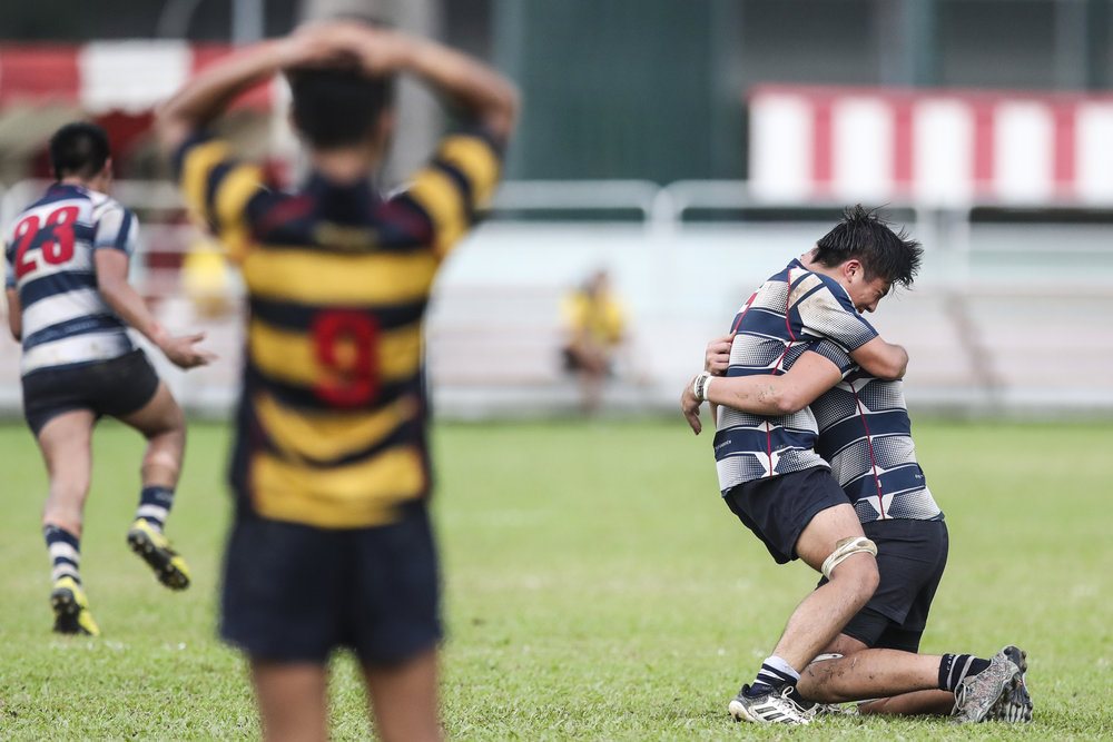 Marcus Chan and James Batt (right) of St. Andrew's Secondary School celebrate their win against Anglo-Chinese School (Independent) during the National Schools boys' 'B' Division rugby final at Queenstown Stadium on March 28, 2018 in Singapore. (Photo © Yong Teck Lim/Red Sports)