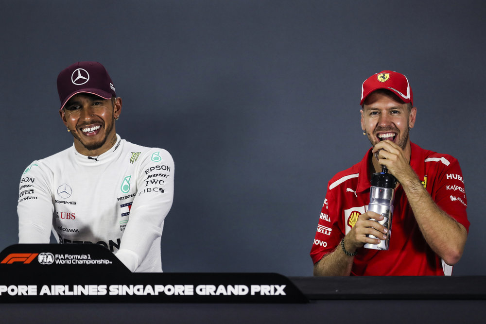 Mercedes driver Lewis Hamilton, left, of Britain and Ferrari driver Sebastian Vettel of Germany laugh during a press conference following the Singapore Formula One Grand Prix at the Marina Bay City Circuit in Singapore, Sunday, Sept. 16, 2018. (AP Photo/Yong Teck Lim)