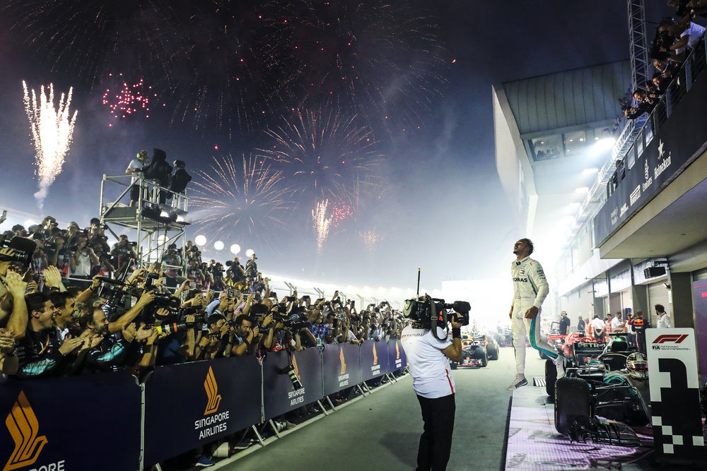 Mercedes driver Lewis Hamilton of Britain leaps off his car as he celebrates after winning the Singapore Formula One Grand Prix at the Marina Bay City Circuit in Singapore, Sunday, Sept. 16, 2018. (AP Photo/Yong Teck Lim)