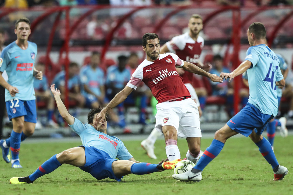 Arsenal's Henrikh Mkhitaryan, center, controls the ball against Atletico Madrid's Andres Solano, left, and Mikel Carro during the International Champions Cup match between Arsenal and Atletico Madrid in Singapore, Thursday, July 26, 2018. (AP Photo/Yong Teck Lim)