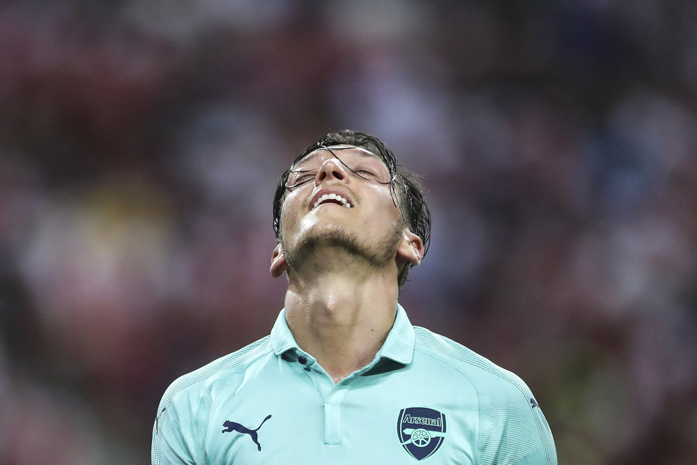 Arsenal's Mesut Ozil reacts after missing an attempt during the International Champions Cup match between Arsenal and Paris Saint-Germain in Singapore, Saturday, July 28, 2018. (AP Photo/Yong Teck Lim)