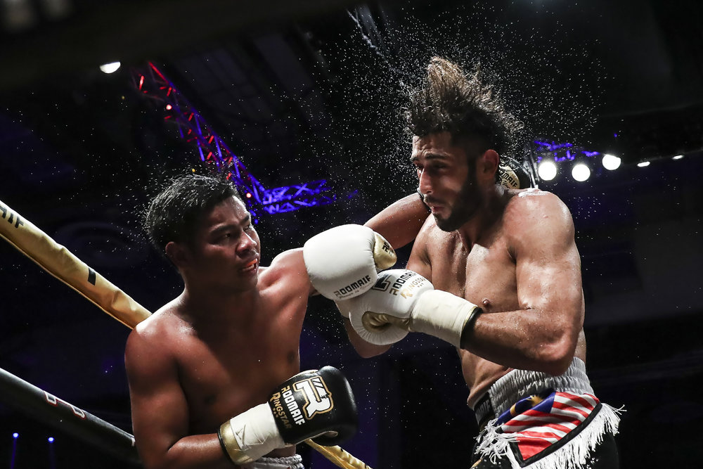 Natthawut Masamin of Thailand (R) punches Mirage Khan of Malaysia during their WBC Asia Continental light heavyweight title fight at the Singapore Indoor Stadium on September 29, 2018.
