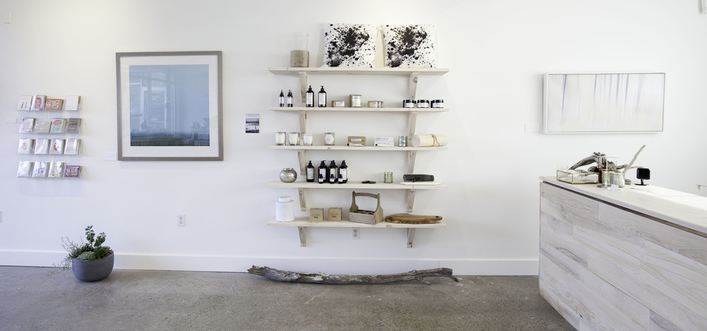 The east wall of the store, showcasing the shelving holding imported Swedish apothecary items and Linnéa candles together with other items for sale in my store. On the walls photography and greeting cards. To the right my custom-built checkout counter.