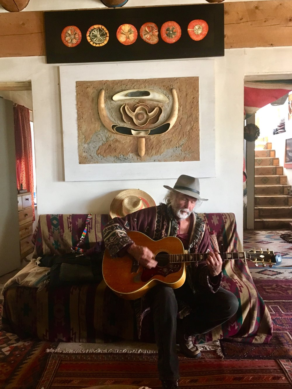 Anselm, playing us a song about his 30 year old mistress below his gourd art work