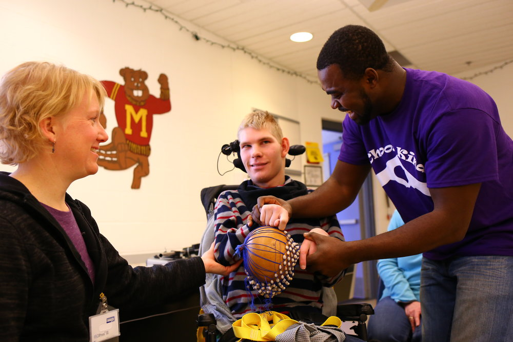 A teacher at the Minnesota School for the Blind works with COMPAS artist Christian Adeti and a student during a West African drumming workshop