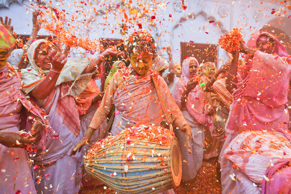 Women dance as they throw flowers at a widow's ashram in the northern state of Uttar Pradesh