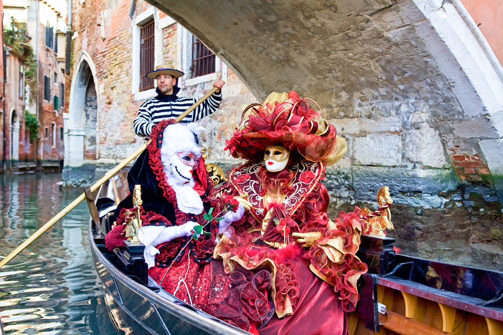 Women in elaborate Venetian masks and costumes enjoying a gondola ride during Carnival