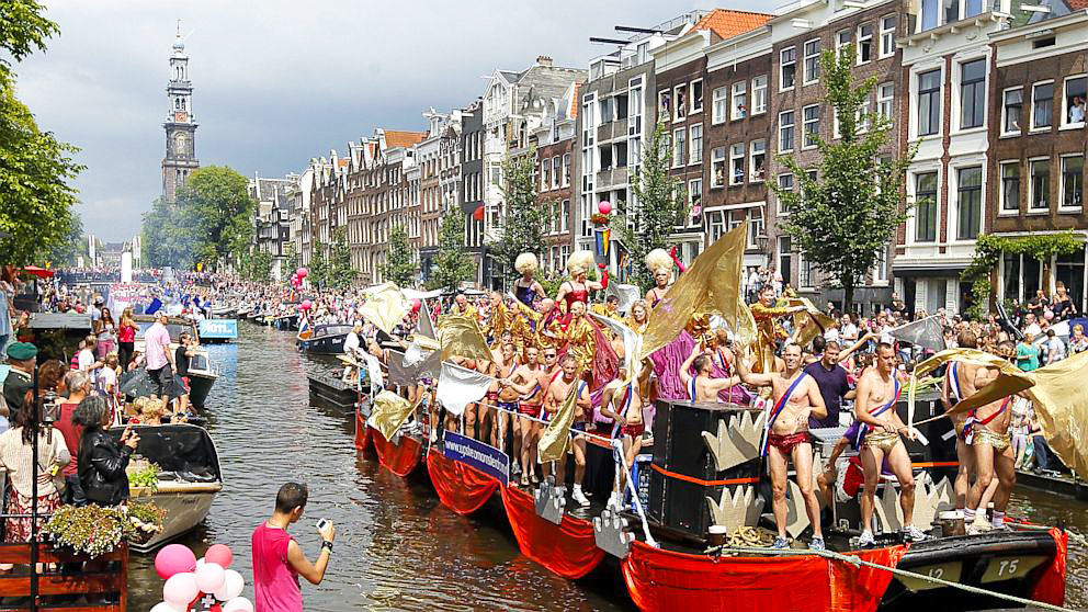 Supporters line the canal to watch the floats of the Amsterdam Gay Pride Parade