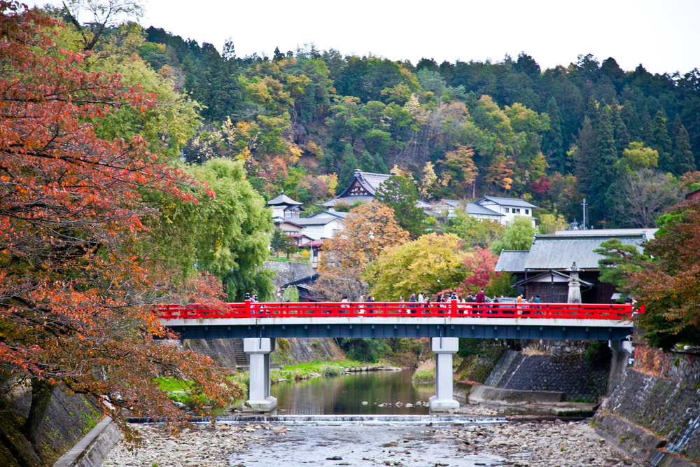 Takayama 's famous red bridge linking the modern side of town to the traditionally preserved districts