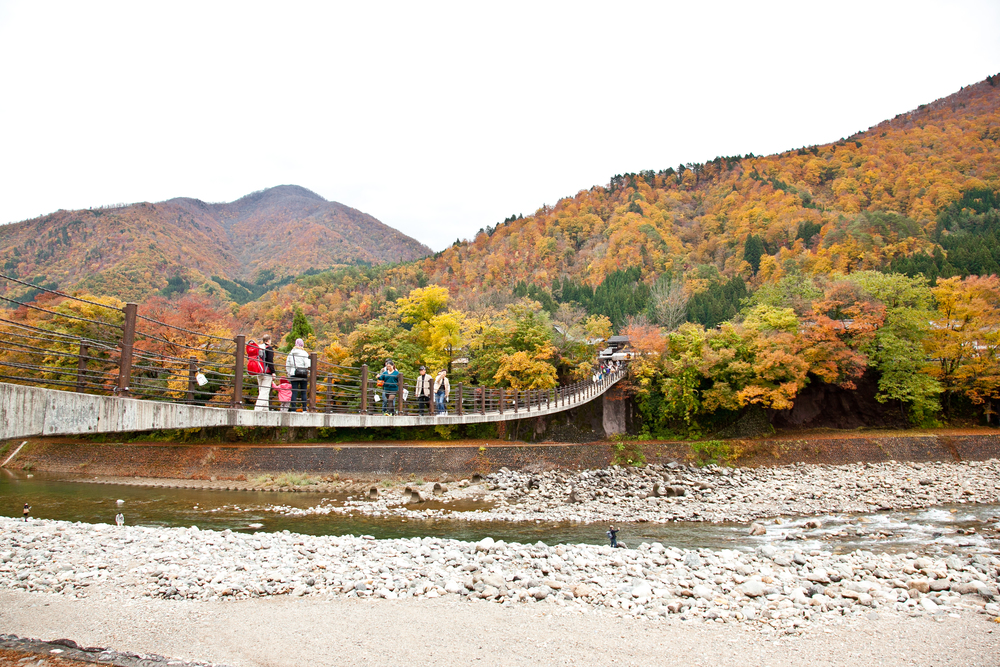 After arriving in Shirakawa-go by car, a suspension walking bridge brings you across the river into the village