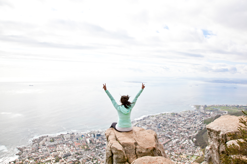 Sitting on the edge of Lion's Head in Cape Town, South Africa