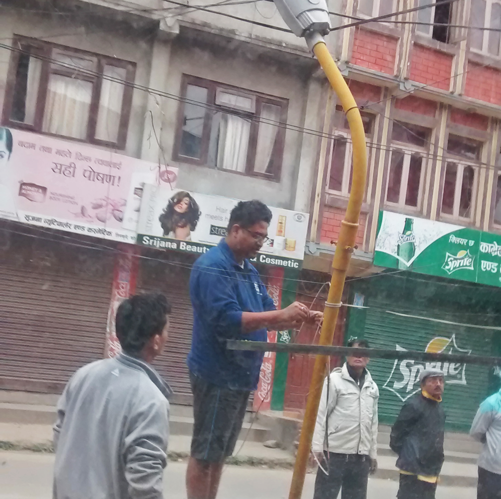 Engineers Avi and Kushal fixing a solar lamp to give a Kathmandu street light after sundown
