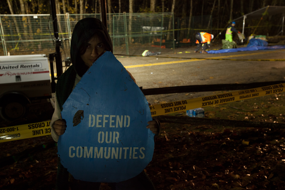 A young Burnaby resident stands behind the injunction line as Kinder Morgan begins to drill a borehole in the Burnaby Mountain Conservation Area.