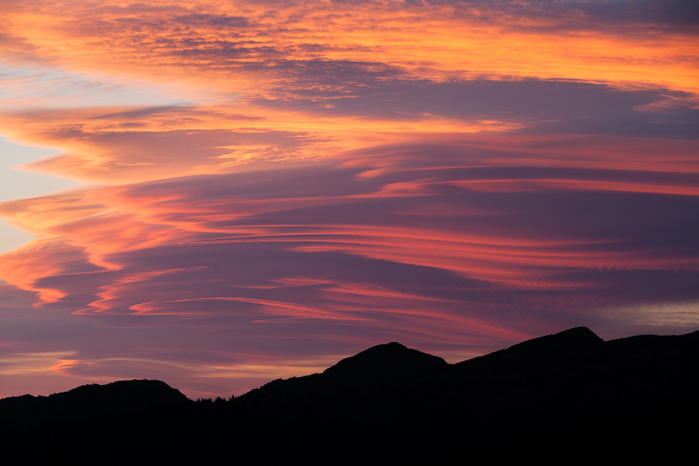 A vibrant sunset lights up lenticular clouds in Manning Provincial Park, B.C, Canada.  Image ©Connor Stefanison