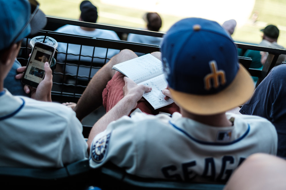 A man is keeping stats at a Mariners baseball game at Safco Field in Seatlle