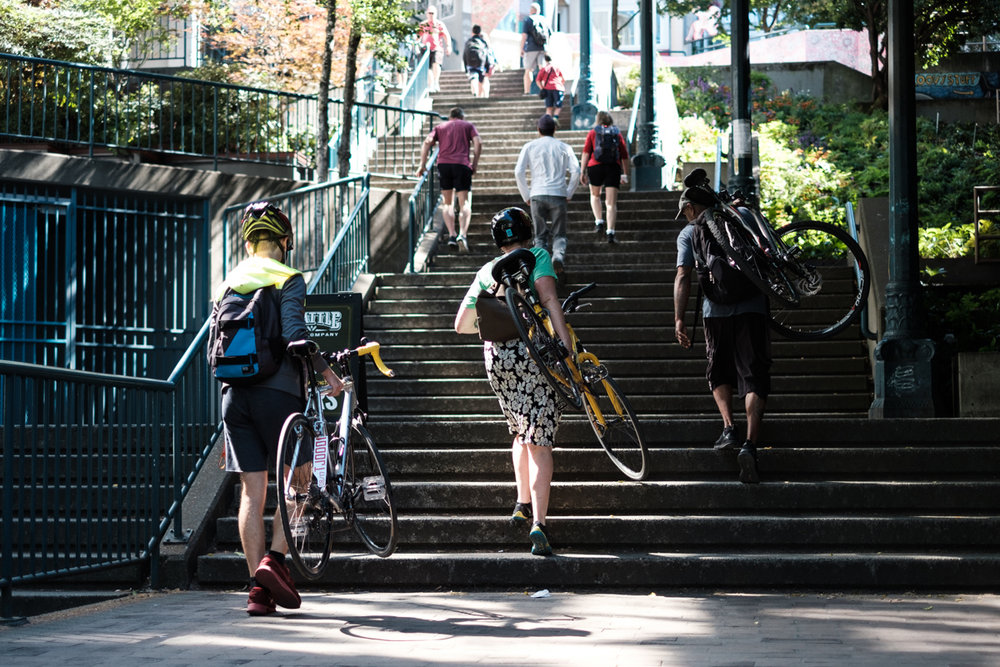 Three young adults carry their bikes up a staircase in Seattle